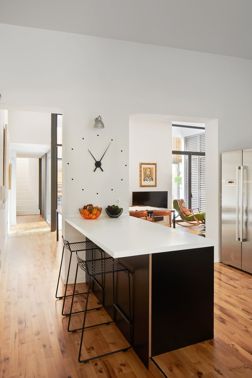 Kitchen, Wall, Laminate, Metal, Engineered Quartz, Porcelain Tile, Medium Hardwood, and Microwave Kitchen island   Kitchen Laminate Engineered Quartz Photos from Conversion of a ground-floor publisher's warehouse into a residence and atelier for an artist-architect couple