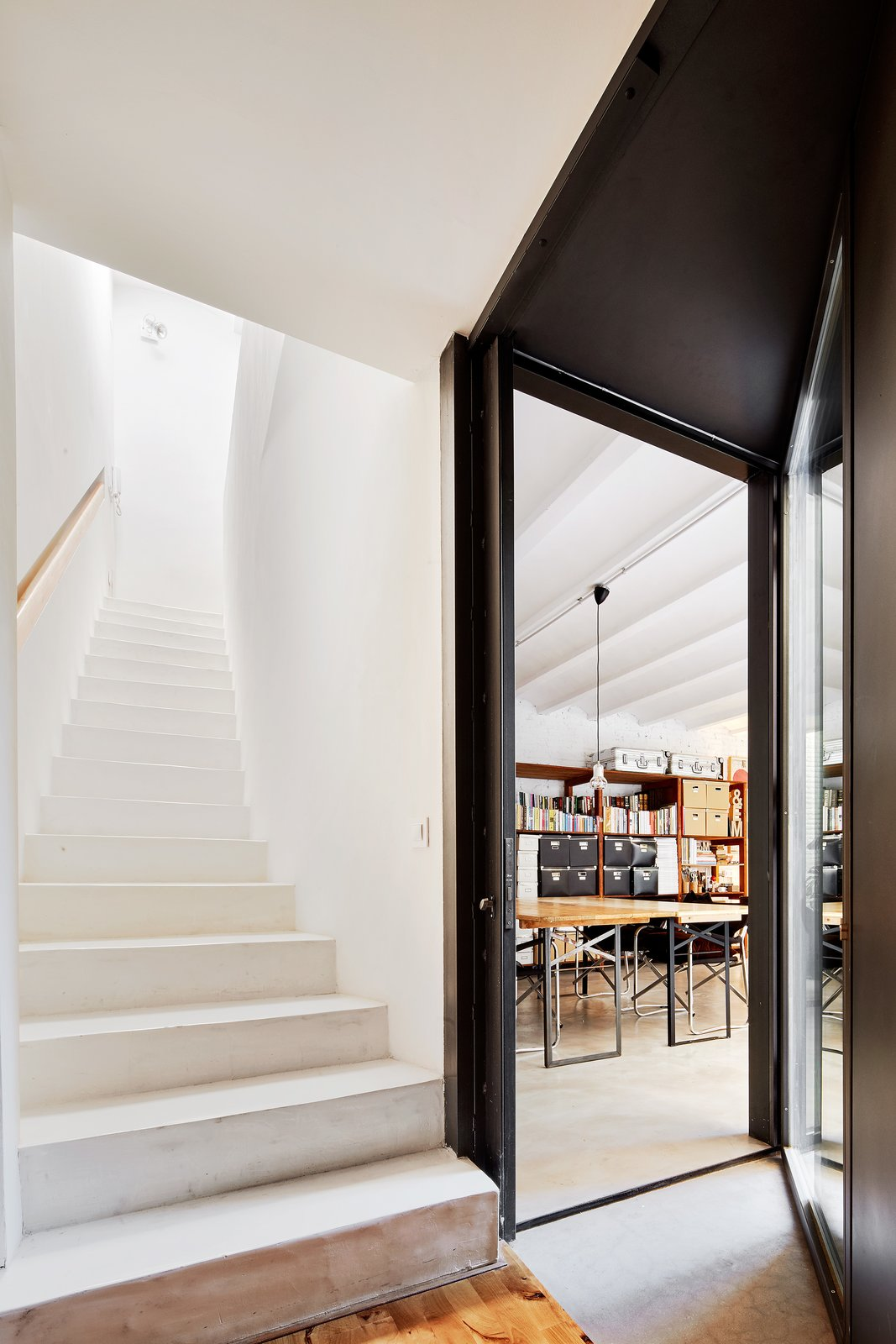 Staircase, Concrete, and Wood Staircase and the extended passageway  Staircase Wood Concrete Photos from Conversion of a ground-floor publisher's warehouse into a residence and atelier for an artist-architect couple