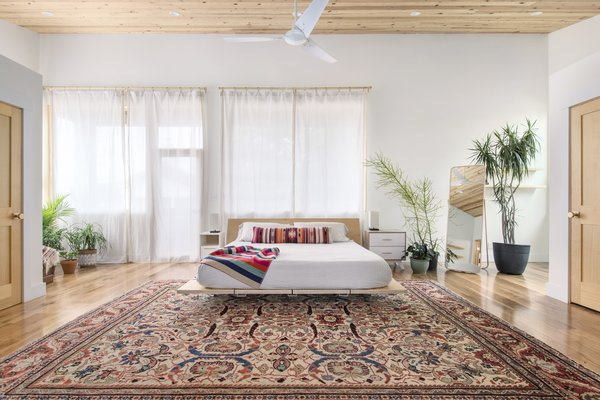 The master bedroom centers a bed frame by Floyd and a vintage rug.