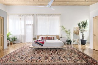 The master bedroom with bed frame by Floyd and vintage rug.
