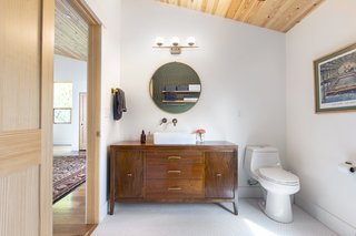 Vintage furniture used as a bath vanities saved on the budget.