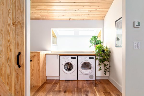 A compact washer and dryer slide under a white oak counter for folding clothes.