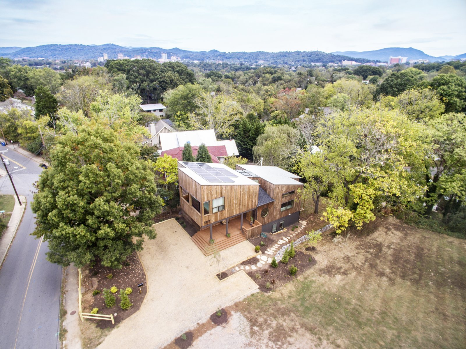 Exterior, Metal Roof Material, House Building Type, Shed RoofLine, and Wood Siding Material Solar panels populate the upper roof and a double height atrium in the middle helps to breakup the home's massing.   Westwood House