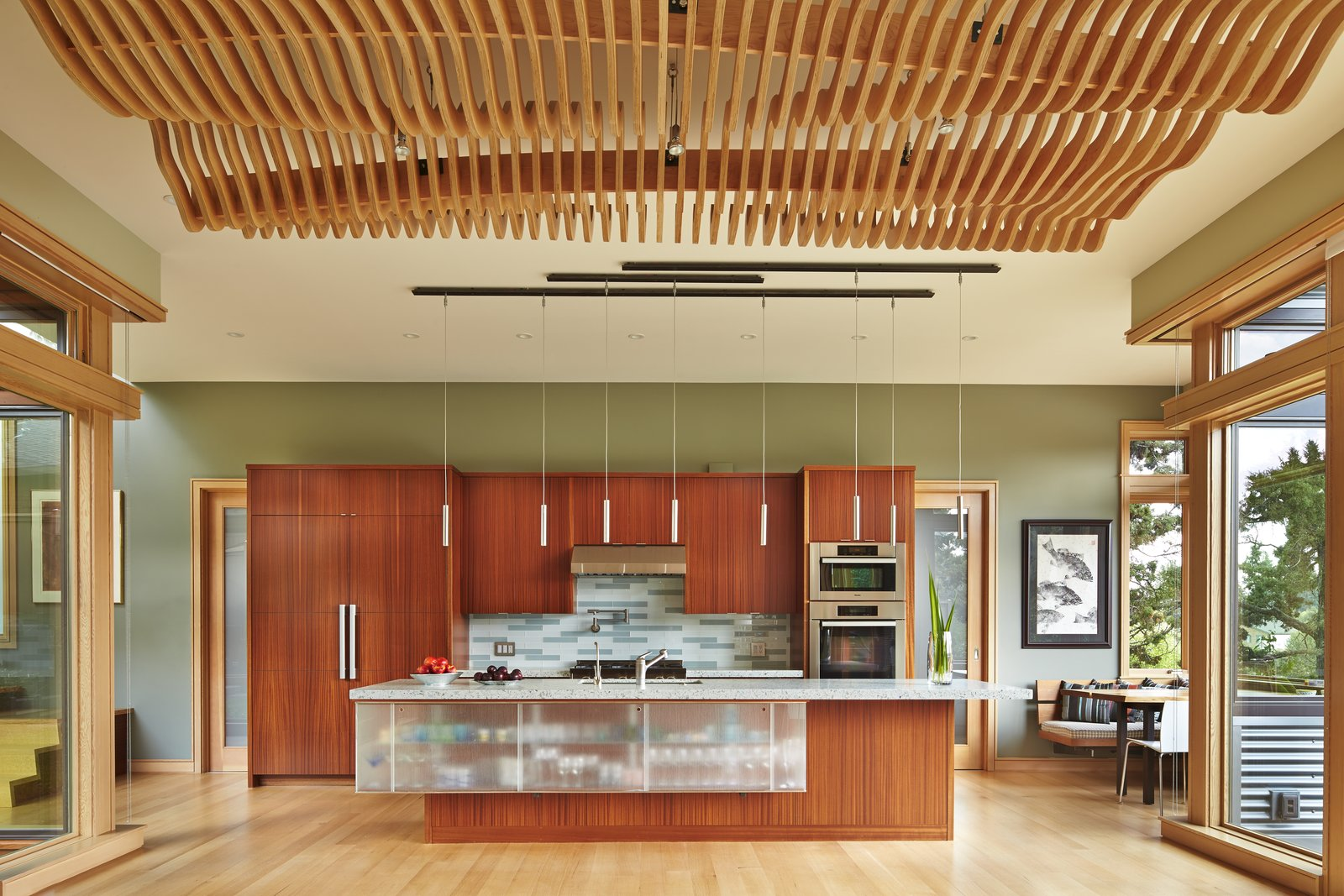 Kitchen, Glass Tile Backsplashe, Ceiling Lighting, Wood Cabinet, Wall Oven, Light Hardwood Floor, Cooktops, Refrigerator, Undermount Sink, Pendant Lighting, and Engineered Quartz Counter Kitchen with undulating wood screen ceiling over dining area  DESCHUTES House by FINNE Architects