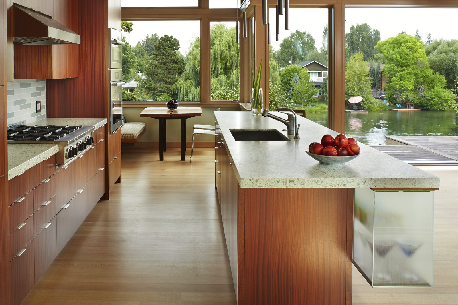 Kitchen, Glass Tile Backsplashe, Refrigerator, Wall Oven, Cooktops, Undermount Sink, Ceiling Lighting, Light Hardwood Floor, Wood Cabinet, and Engineered Quartz Counter View of kitchen and breakfast alcove  DESCHUTES House by FINNE Architects