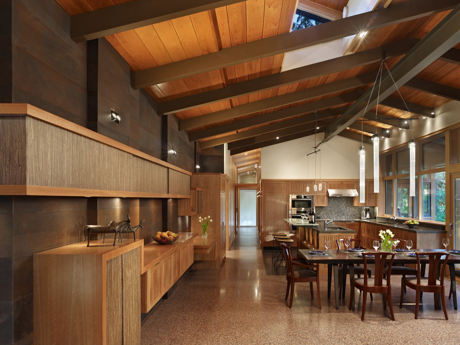 Dining, Table, Pendant, Chair, Terrazzo, Two-Sided, and Ceiling View of dining and kitchen areas with weathered steel wall, cherry cabinets and custom light fixtures.  Best Dining Ceiling Terrazzo Table Photos from Lake  Forest Park Mid Century Renovation