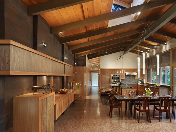 View of dining and kitchen areas with weathered steel wall, cherry cabinets and custom light fixtures.