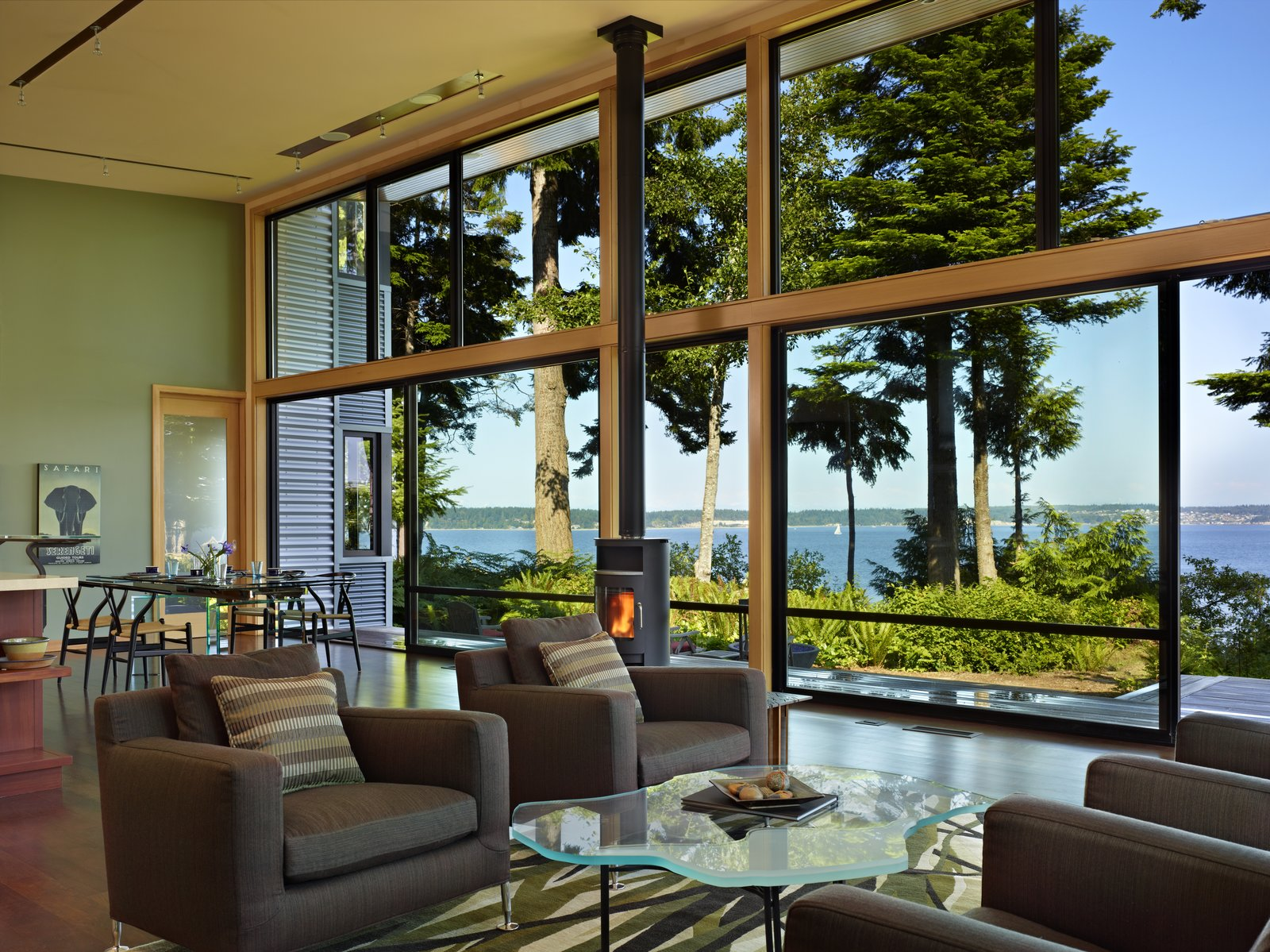 Living Room, Sofa, Dark Hardwood Floor, Wood Burning Fireplace, Chair, Coffee Tables, and Ceiling Lighting Main living space, which feels like an open porch due to the large sliding glass panels  Port Ludlow House by FINNE Architects
