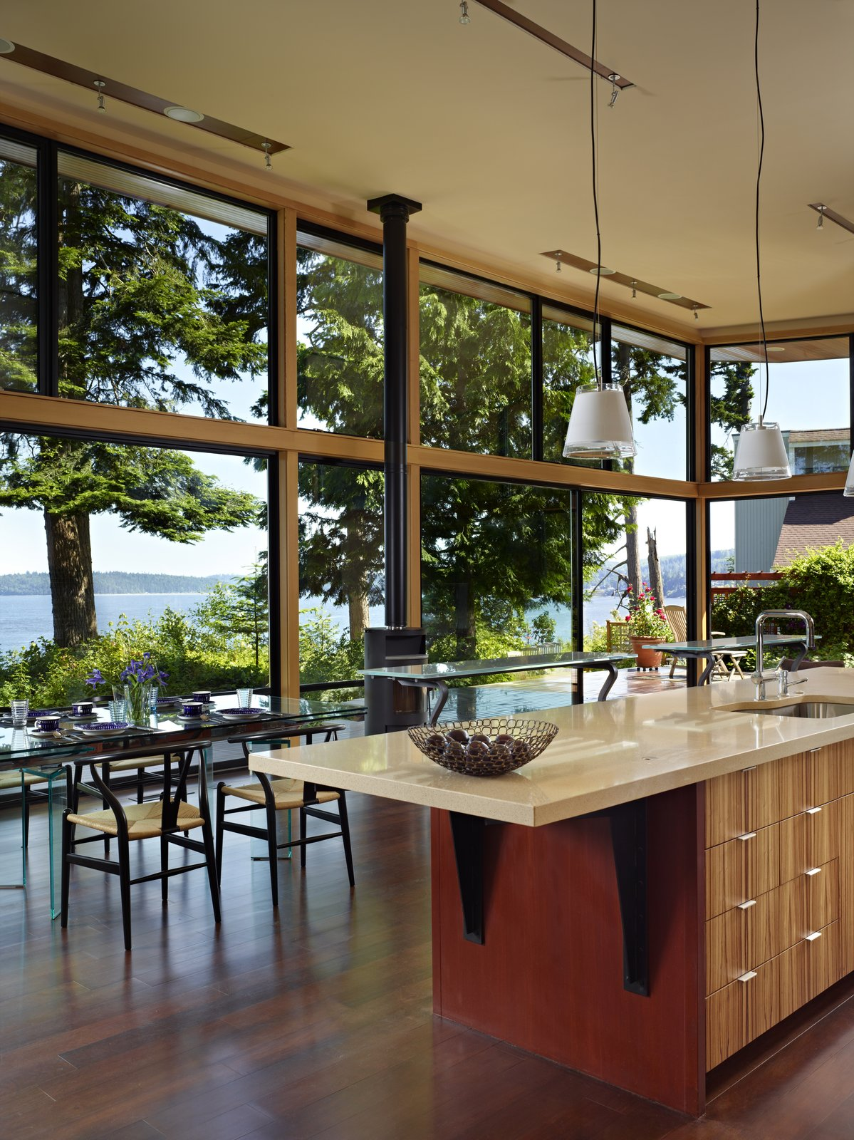 Kitchen, Porcelain Tile Backsplashe, Pendant Lighting, Engineered Quartz Counter, Ceiling Lighting, Wall Oven, Cooktops, Refrigerator, Wood Cabinet, Dark Hardwood Floor, and Drop In Sink Interior view of kitchen and dining spaces  Port Ludlow House by FINNE Architects