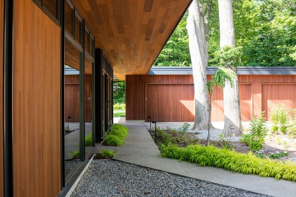 Situated on the site to carefully preserve six 160 year-old white and red oak trees, the streetward elevation of the home maintains the built edge of the existing streetscape.