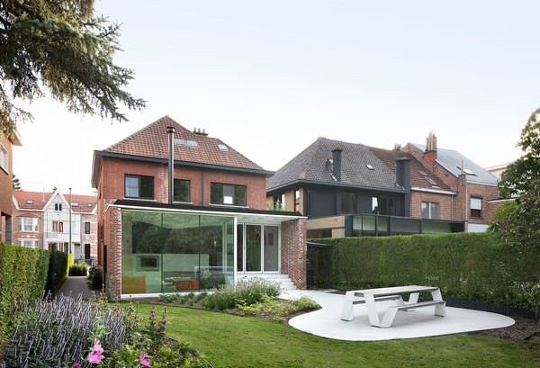 Outdoor, Flowers, Hardscapes, Garden, Small Patio, Porch, Deck, Back Yard, Gardens, Vertical Fences, Wall, Concrete Patio, Porch, Deck, Shrubs, Trees, and Grass New addition and patio from outdoor garden: the concrete terrace extends into the garden, and receives daylight over the house from the southern sun.  Best Photos from Leuven Residential Addition