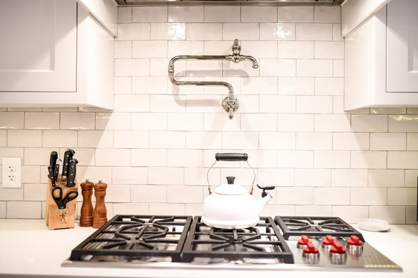 We'd never knock the classic white backsplash. They come in a range of styles and finishes, from very simple and consistent to handmade and slightly irregular, and work with dark kitchen cabinets just as well as light or white cabinets. In this kitchen, the white countertop matches the white glossy tile backsplash from Porcelain and More.