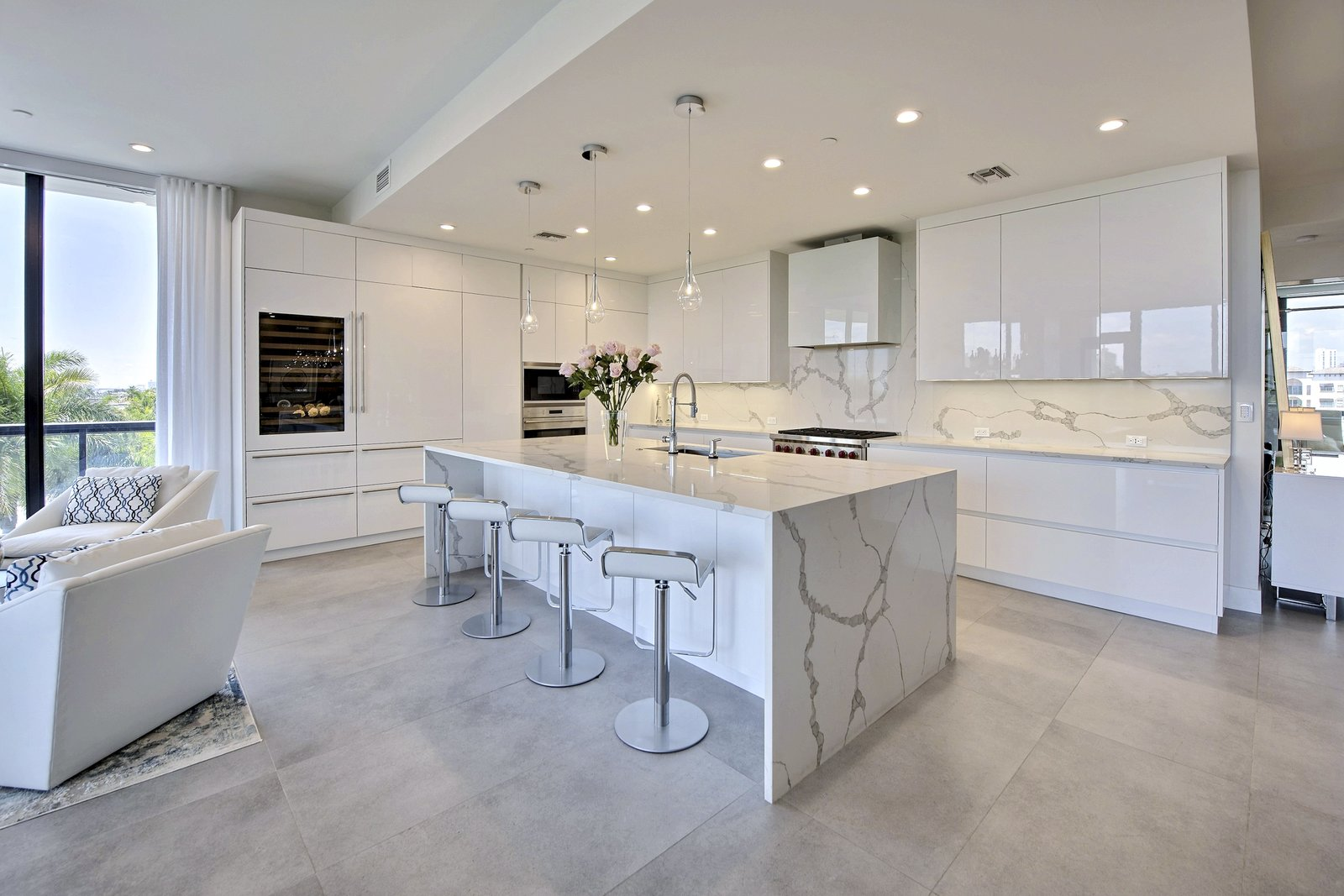 The white quartz counters and backsplash boast a clean, open design. This kitchen's sophisticated feel is perfect for everything from cocktail parties to chef-inspired dinners.  Luxury Florida Penthouse with Private Boat Slip Up for Auction