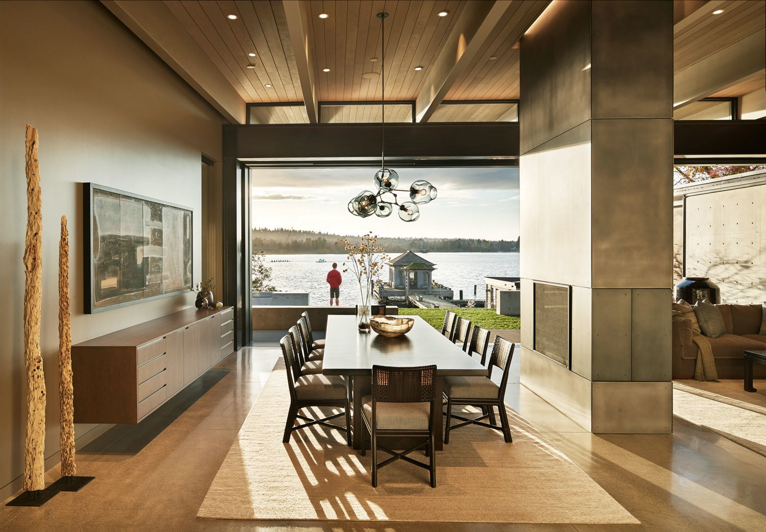 Dining Room, Two-Sided Fireplace, Pendant Lighting, Table, Concrete Floor, Storage, Chair, and Ceiling Lighting Sweeping views of Lake Washington from the dining room  Union Bay Residence by NB Design Group