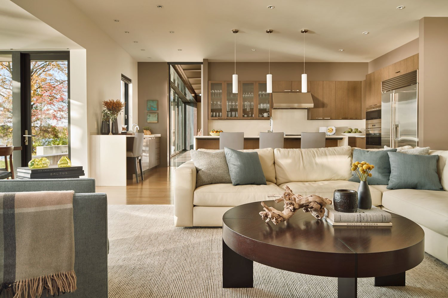 Kitchen, Light Hardwood Floor, Refrigerator, Range Hood, Wood Cabinet, Engineered Quartz Counter, Pendant Lighting, Recessed Lighting, Wall Oven, and Cooktops A large leather sectional grounds the family room  Union Bay Residence by NB Design Group