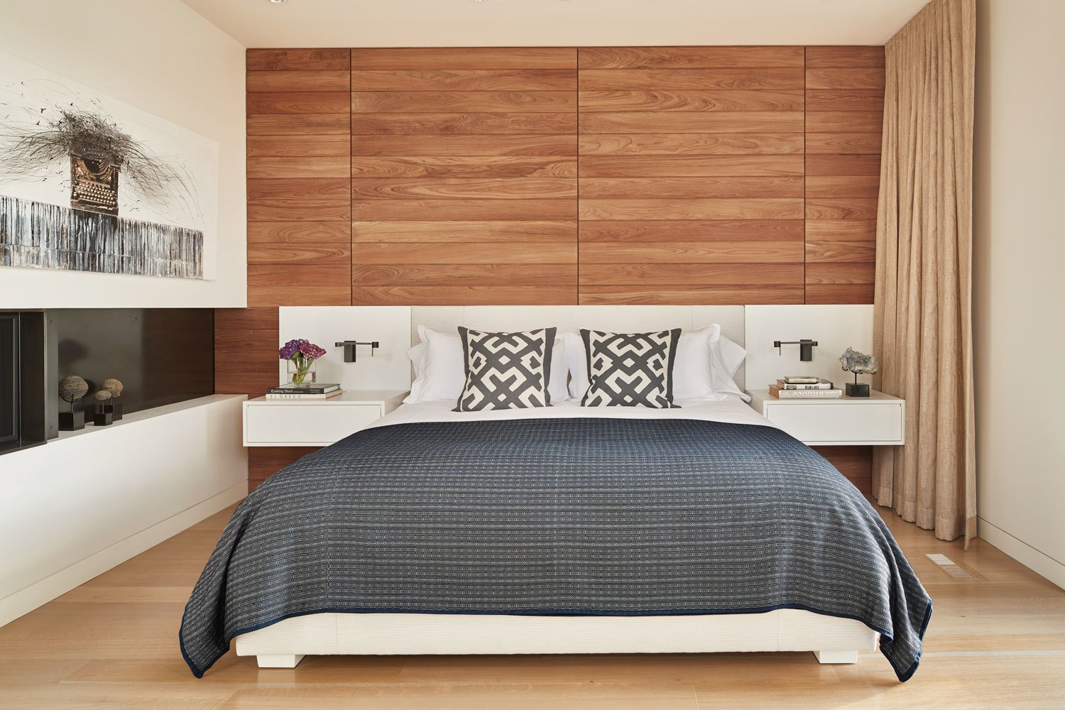 Bedroom, Bed, Wall Lighting, and Light Hardwood Floor The master bedroom features a wall of teak paneling  Union Bay Residence by NB Design Group
