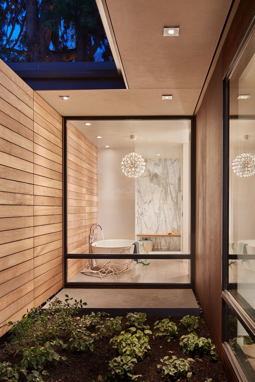 Bath Room, Pendant Lighting, Marble Wall, and Freestanding Tub The teak paneling continues  through to the exterior  Union Bay Residence by NB Design Group