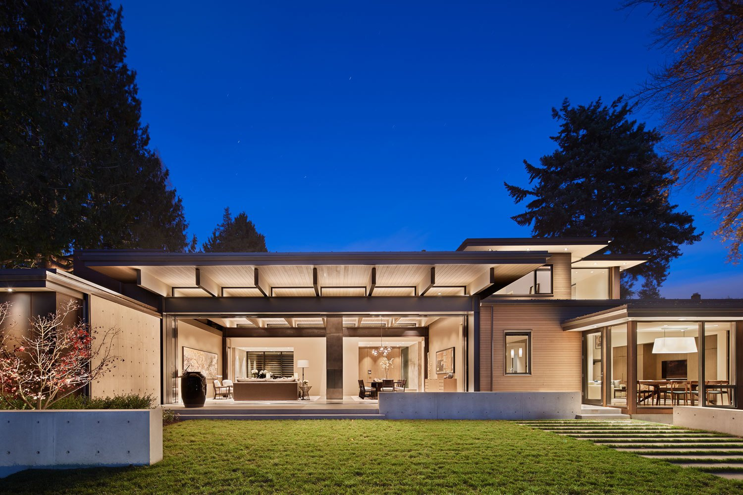 Outdoor, Large Patio, Porch, Deck, Grass, Walkways, Concrete Patio, Porch, Deck, Hardscapes, Trees, Shrubs, and Back Yard An evening view of the home from the lake  Union Bay Residence by NB Design Group