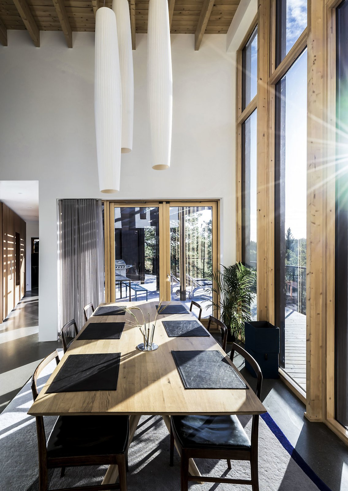 Dining Room, Ceiling Lighting, Table, Concrete Floor, Stools, and Pendant Lighting Dining area flooded with light  Woodland house