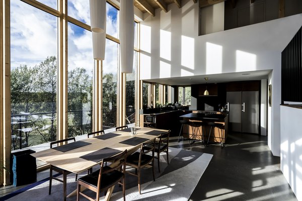Kitchen, Ceiling Lighting, Refrigerator, Wood Backsplashe, Undermount Sink, Wood Cabinet, Pendant Lighting, Wood Counter, Dishwasher, and Concrete Floor Kitchen view open plan living - perfect for social people  Woodland house