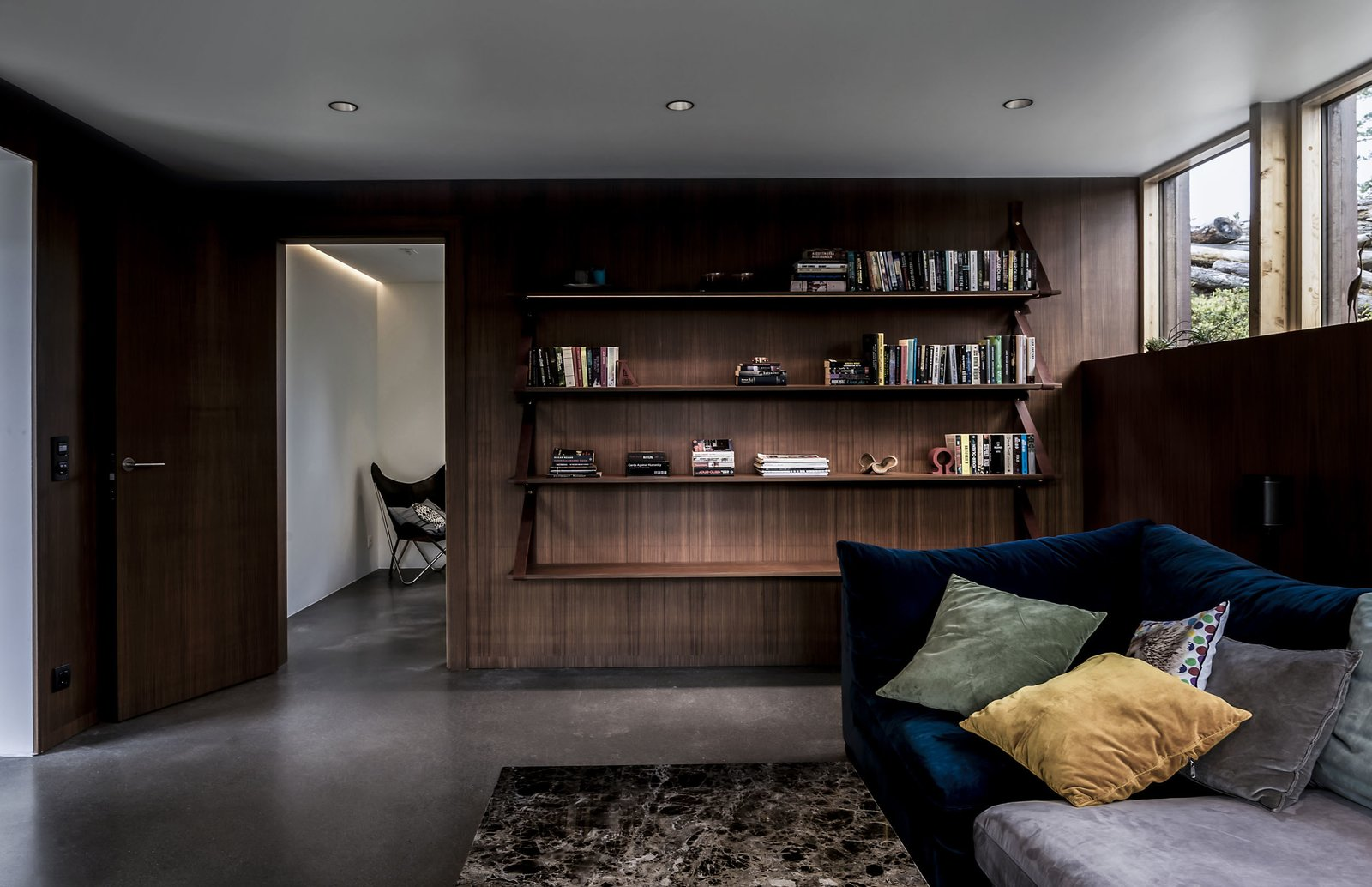 Living Room, Ceiling Lighting, Sofa, Recessed Lighting, Concrete Floor, and Bookcase Simple yet beautiful DIY shelves made from leather and mahogany with hidden LED strips  Woodland house