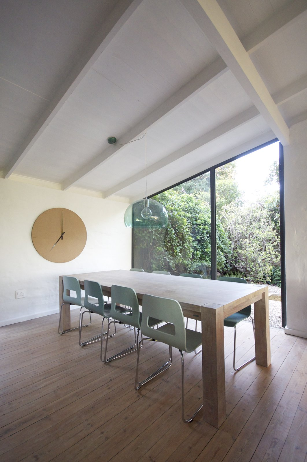 Dining Room, Pendant Lighting, Table, Chair, Light Hardwood Floor, and Ceiling Lighting the dining area with a view of the garden  Grey House