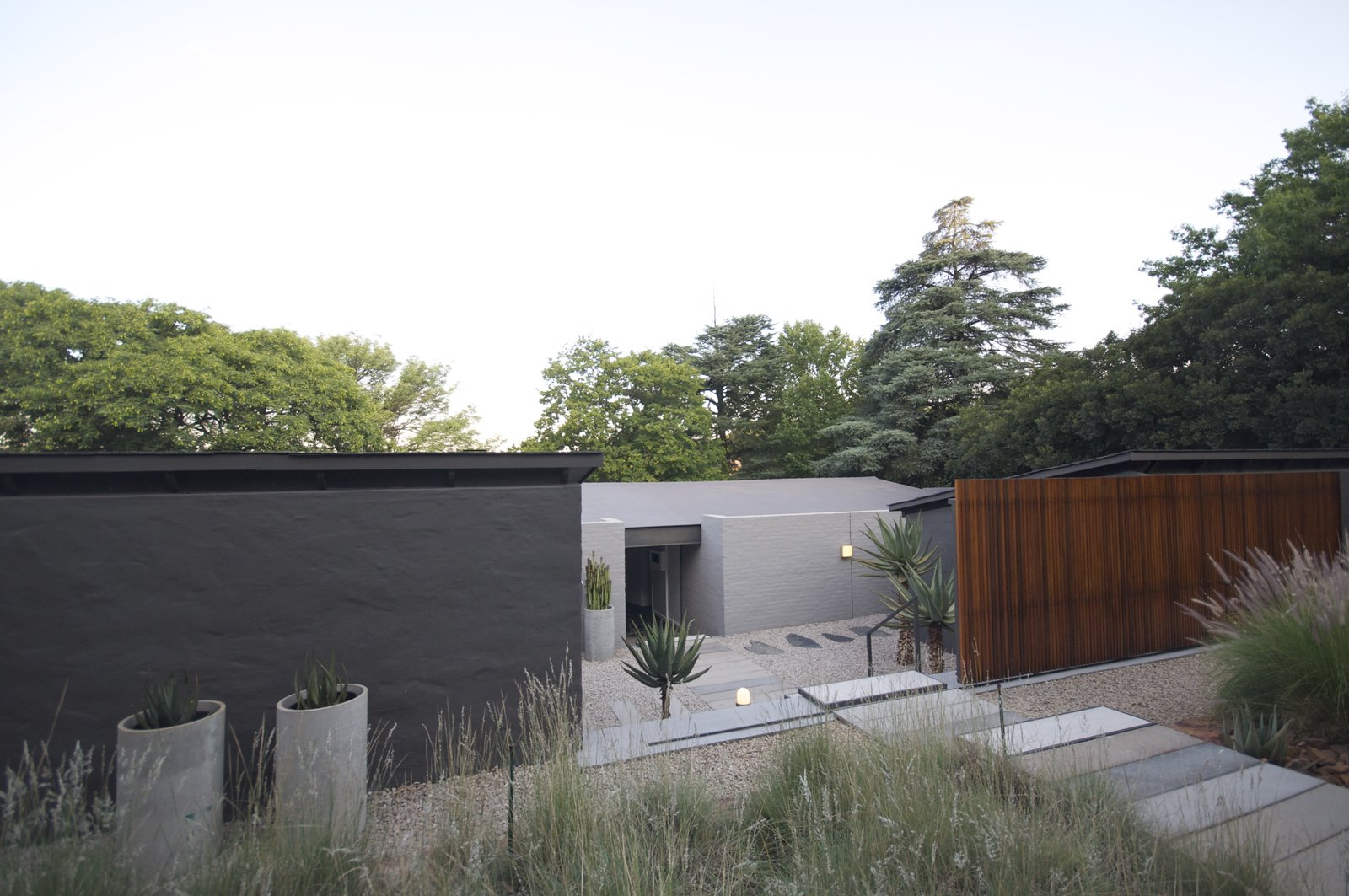Outdoor, Trees, Garden, Front Yard, Grass, and Walkways Entrance view: An automated timber screen gives the entrance courtyard privacy from the street. Mature trees form a lush backdrop to the house with the front garden landscaped with chipped stone, grasses and aloes. Concrete storm water pies is placed as focal planters.  Grey House