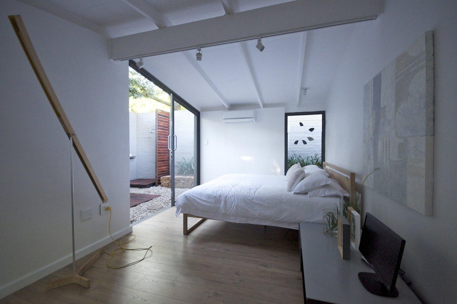 Bedroom, Bed, Ceiling Lighting, Light Hardwood Floor, and Track Lighting main bedroom  Grey House
