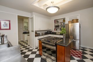 Owners have kept the retro kitchen black and white tile floor, butler pantry, and swinging door