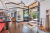 Modern home with Living Room, Ceiling Lighting, Table, Dark Hardwood Floor, and Accent Lighting. Oversized glass front doors and custom stained glass transom make a statement. Photo 3 of Hawaii Architect's Home in Keauhou Estates
