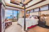 Modern home with Bedroom, Ceiling Lighting, Table Lighting, Dresser, Recessed Lighting, Dark Hardwood Floor, Lamps, Night Stands, Chair, Rug Floor, and Bed. Incredible views from the master suite. Photo 9 of Hawaii Architect's Home in Keauhou Estates