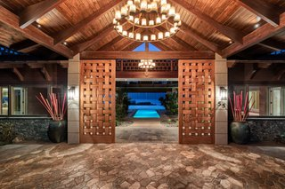 Designed by architect Robert Robinson after a Balinese resort, this Hawaiian estate commands sweeping ocean and multi-island views. The pool is visible, even from the custom front doors, which give off a warm, local vibe through their woven appearance and wood construction.