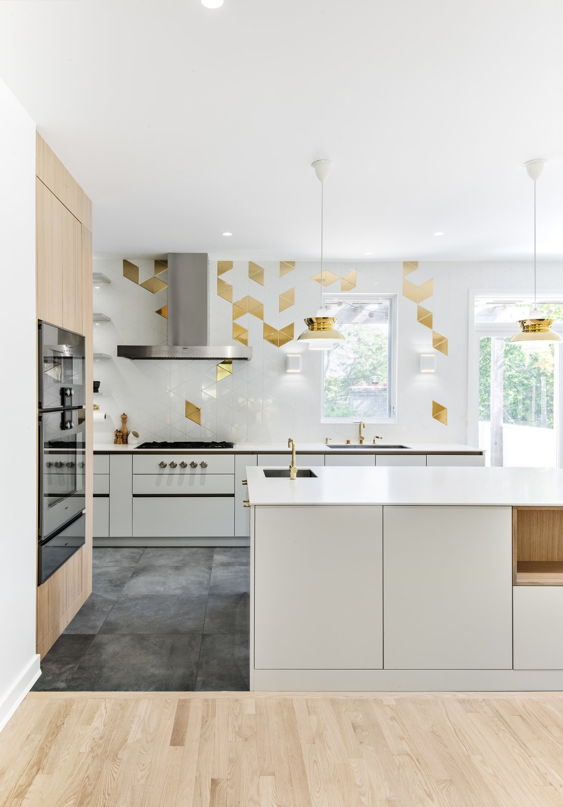 Kitchen, Engineered Quartz, Range Hood, Porcelain Tile, Cooktops, Wall Oven, Undermount, Wood, Ceiling, Pendant, White, Light Hardwood, and Ceramic Tile Kitchen  Kitchen Cooktops Undermount Wall Oven Ceramic Tile White Photos from The Rockcliffe Renovation
