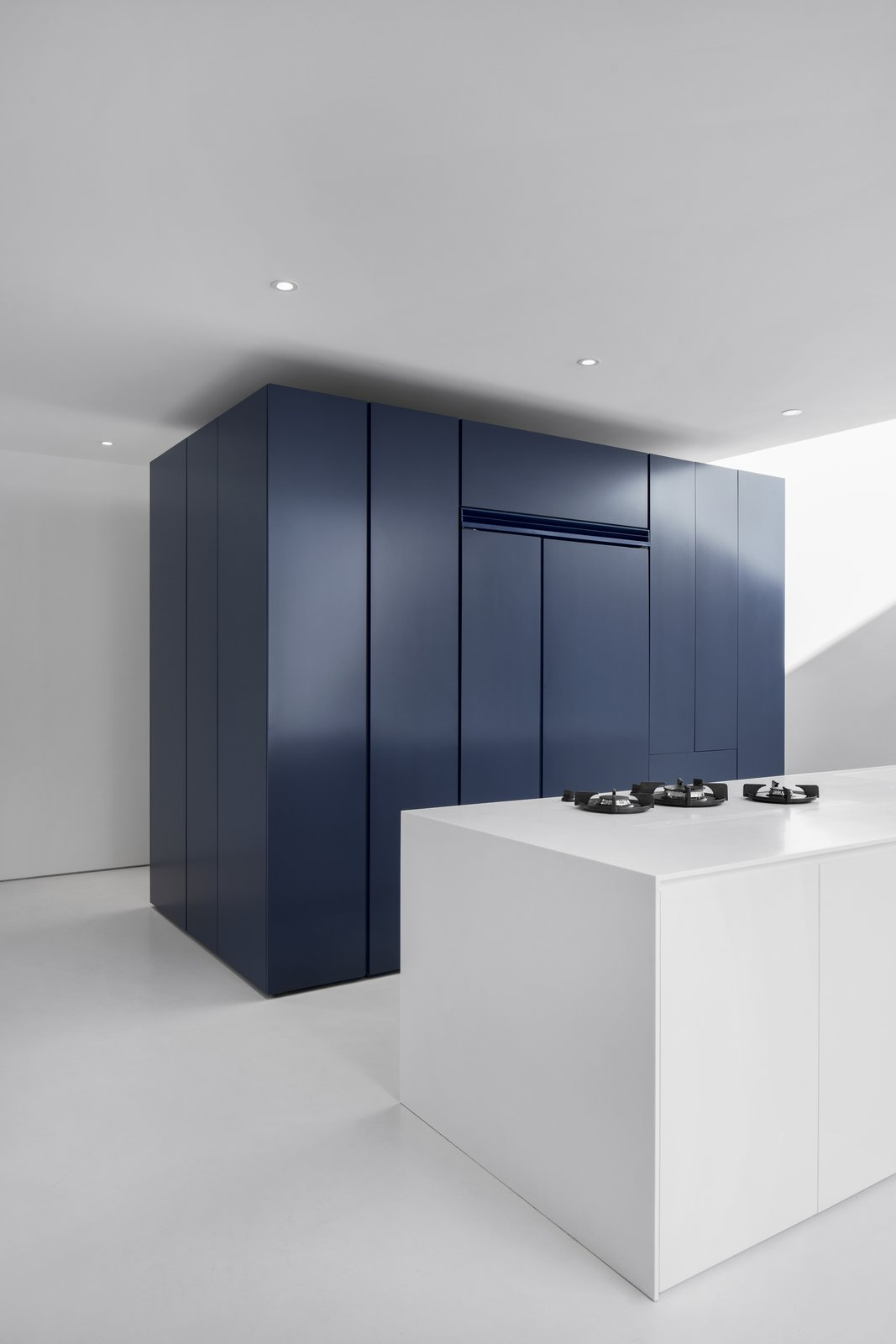 Kitchen, Painted Wood, Undermount, Colorful, Cooktops, Ceiling, and Refrigerator A dark blue block is the central pole of the kitchen area. Deposited directly on the floor, its periphery creates a zone of circulation.  Best Kitchen Undermount Painted Wood Photos from The House on Drolet Street