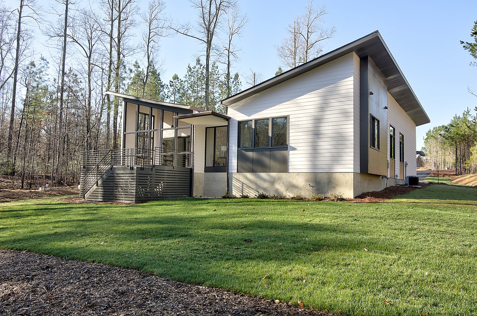 Exterior, Flat RoofLine, Mid-Century Building Type, Wood Siding Material, Shed RoofLine, Shingles Roof Material, House Building Type, and Butterfly RoofLine Exterior Rear  House 23 by Zipper Architecture