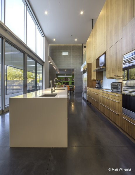 Lofted kitchen, sealed integrally colored concrete floors. The tiny frosted glass window only glows on owners' marriage anniversary for 2 minutes.