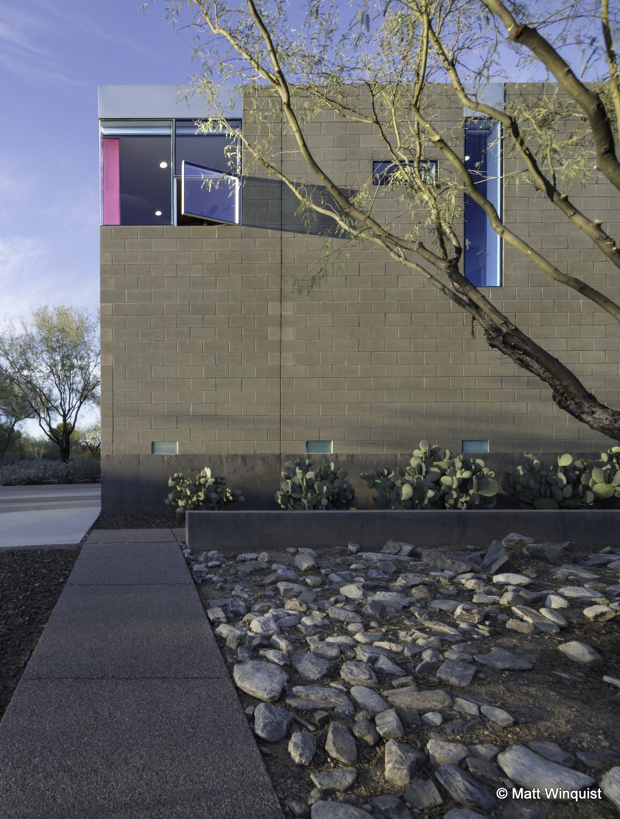 Exterior, Concrete, Metal, Brick, Flat, and House Inspired by the color of Strawberry Hedgehog cactus thriving in the front yard of the house, the window wants to be an abstract flower drawing guests toward the front entrance. The wall lights are abstract luminarias of the southwest landscape.  Exterior Metal Concrete Brick Photos from Essence of the Desert