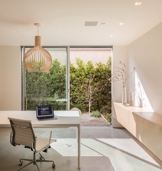 The home office of 19th St. Residence by Ehrlich Yanai Rhee Chaney Architects peeks into the lush side yard.