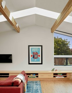Ridge skylights in a vaulted ceiling welcome light into the open living space of the family's home.