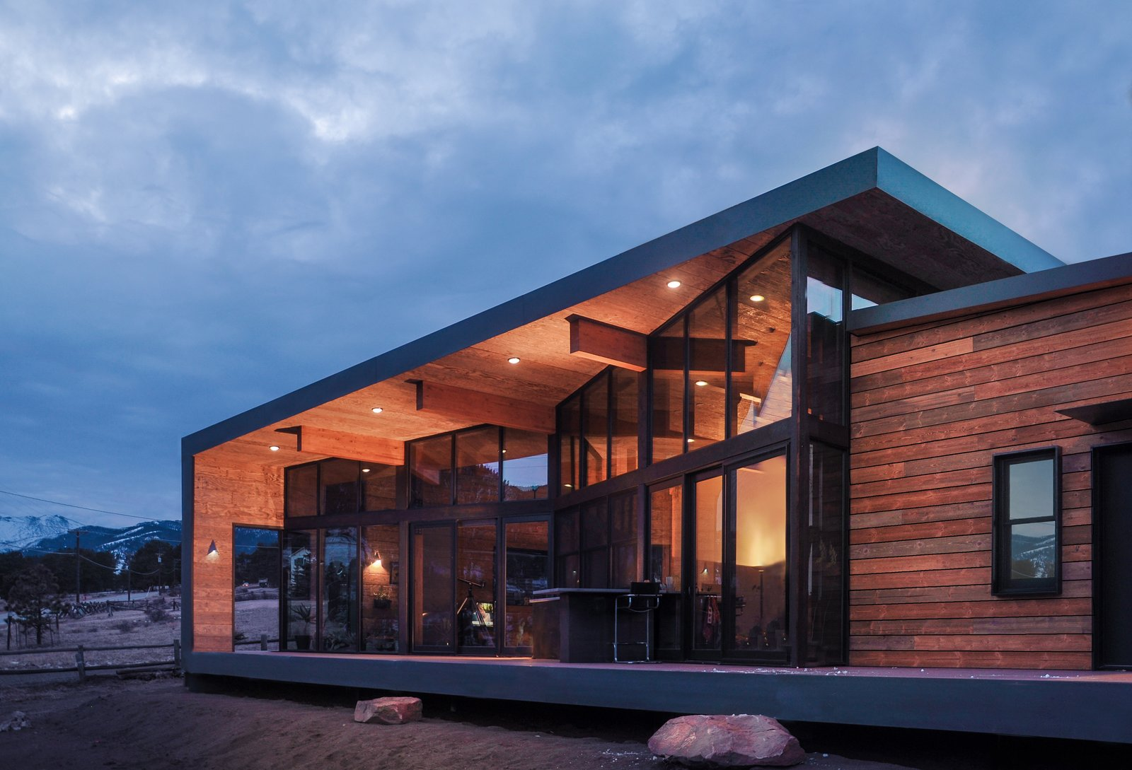 Exterior, House, Glass, Shed, Wood, Metal, and Metal A large window wall folds in to create a spacious deck that wraps up and over to become the roof and overhang of the home.  Best Exterior Shed Metal Metal Photos from Estes Park Residence