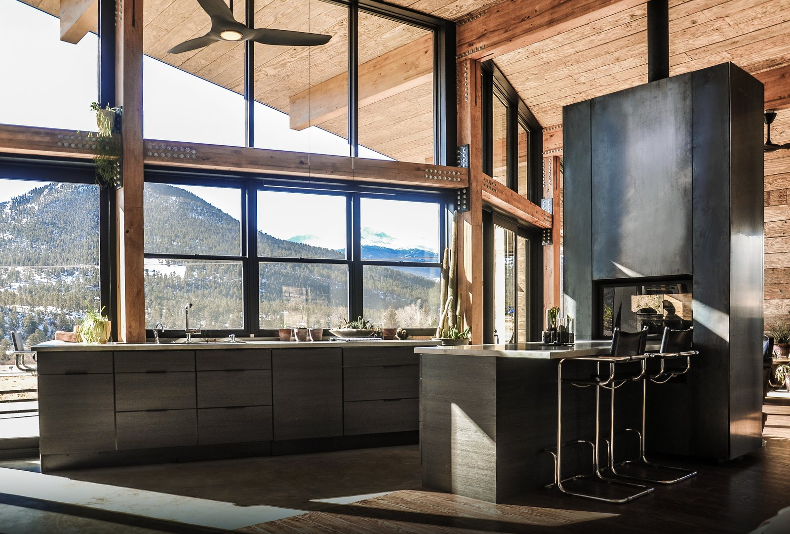 Kitchen, Refrigerator, Microwave, Cooktops, Wood, Dishwasher, Ceiling, Metal, Dark Hardwood, Concrete, Concrete, Range, Wall Oven, Pendant, Concrete, Accent, and Drop In The warm industrial kitchen celebrates views of Rocky Mountain National Park beyond. A see-through, steel fireplace becomes a glowing beacon that warms the kitchen and living room at the heart of the home.   Best Kitchen Pendant Microwave Refrigerator Wall Oven Drop In Wood Dark Hardwood Photos from Estes Park Residence