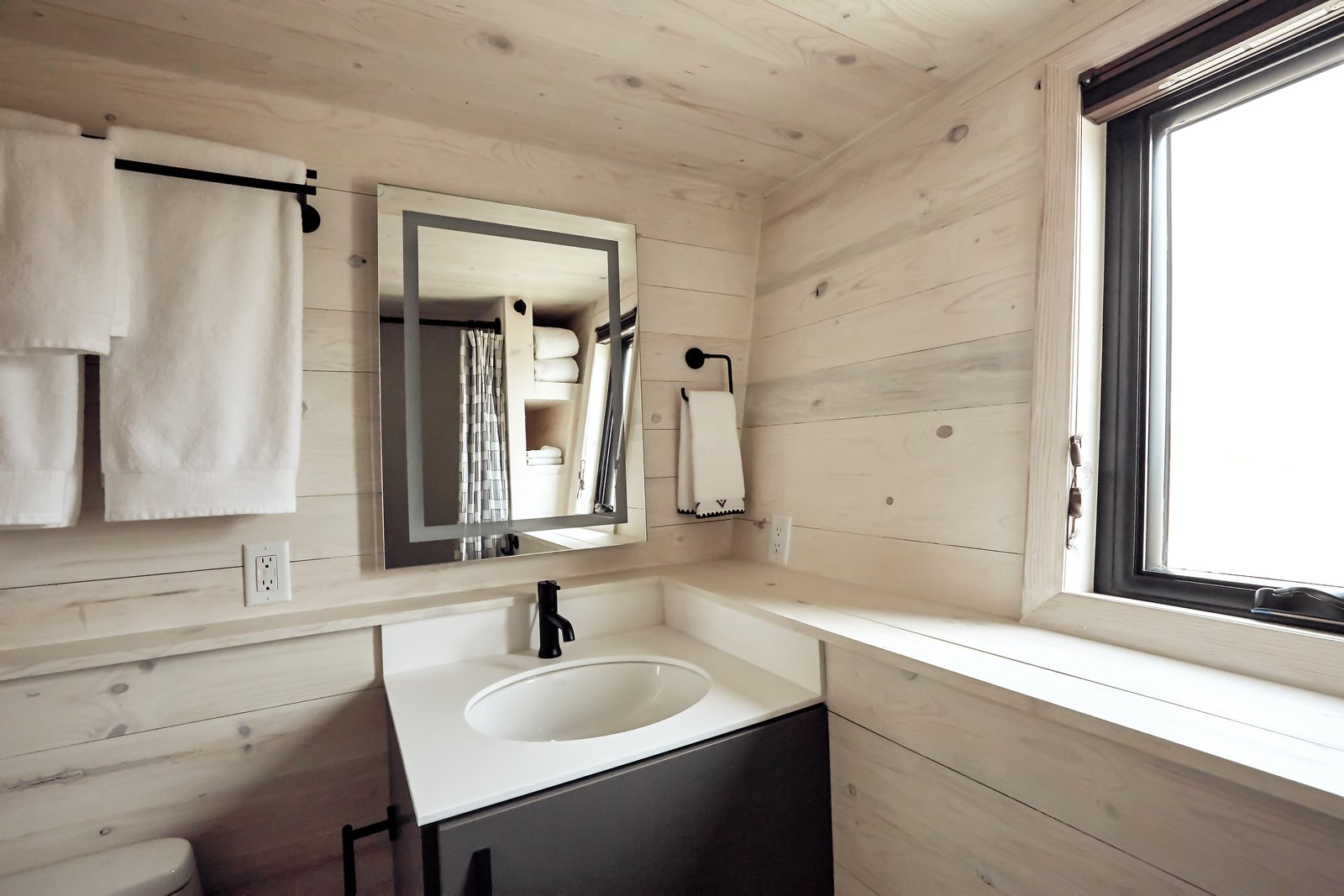 The pine ledge wraps around creating useful storage. Integrated linen nooks can be seen in the lighted mirror's reflection. The bathroom features a one-piece toilet, 30x60 tub and Kohler wall surrounds.  Land Ark RV - Drake by Brian Buzarde