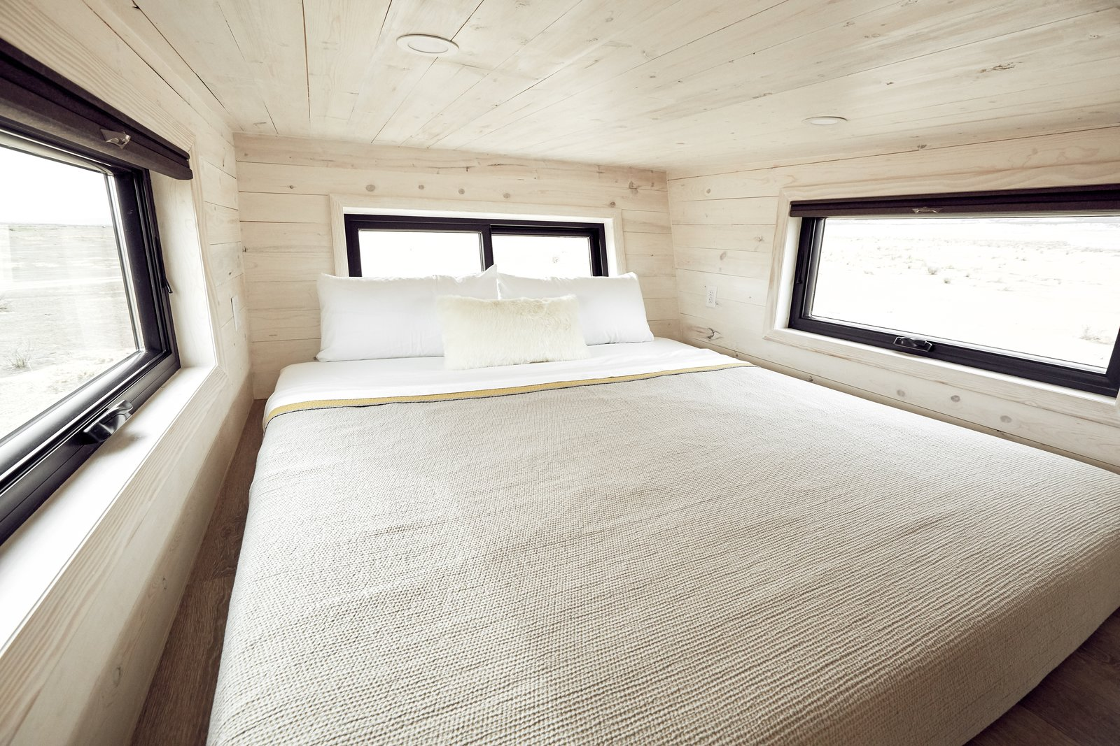 Bedroom, Ceiling Lighting, and Bed The master loft fits a king bed, and features an egress window and two awnings.    Photo 9 of 14 in This Sleek Travel Trailer Is Practically a Cabin on Wheels from Land Ark RV - Drake