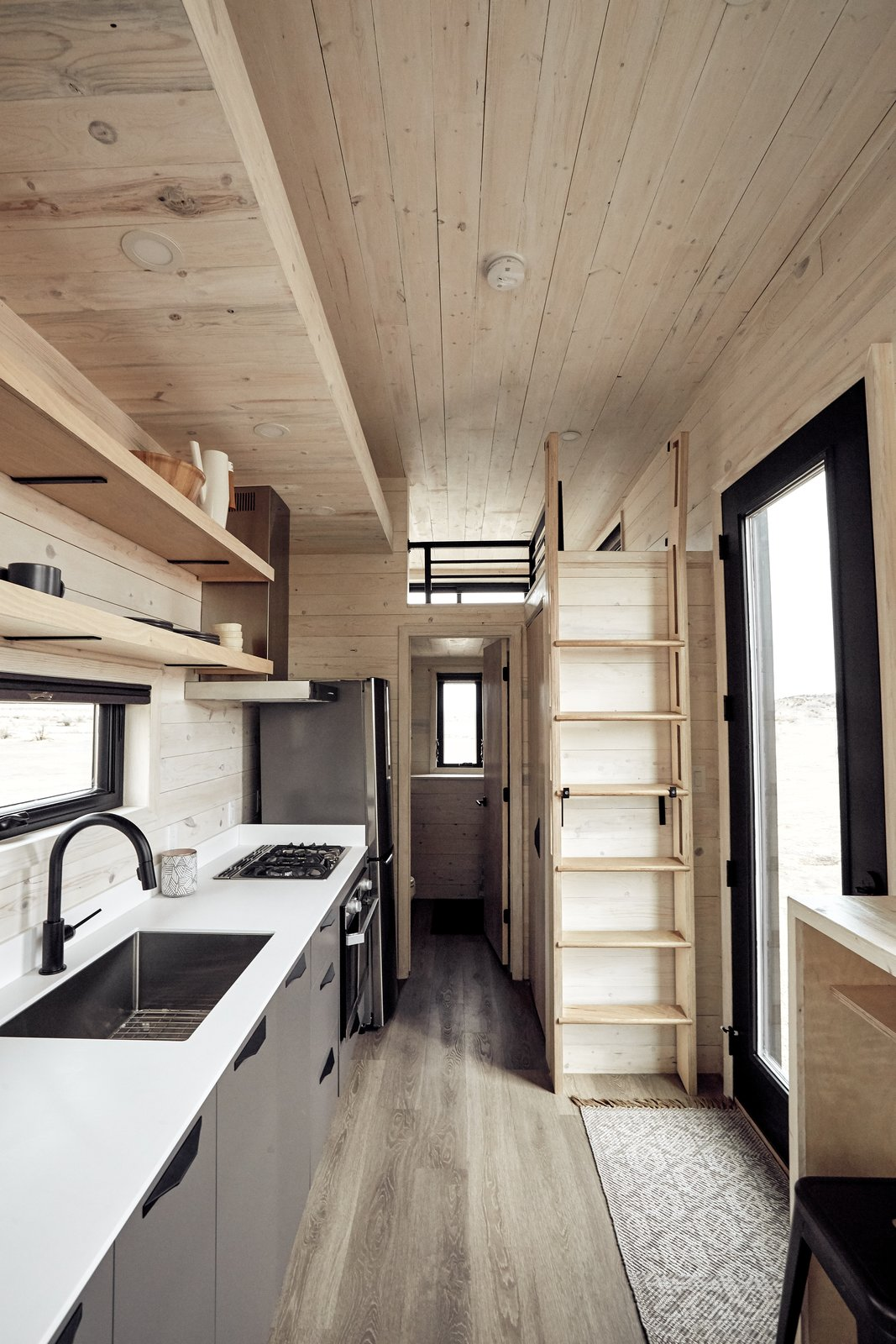 Kitchen, Refrigerator, Ceiling Lighting, Range Hood, Cooktops, Undermount Sink, and Wall Oven The tall ladder lives secured against the wall, but can be attached to either the guest loft or storage soffit, providing access to either.    Photo 6 of 14 in This Sleek Travel Trailer Is Practically a Cabin on Wheels from Land Ark RV - Drake