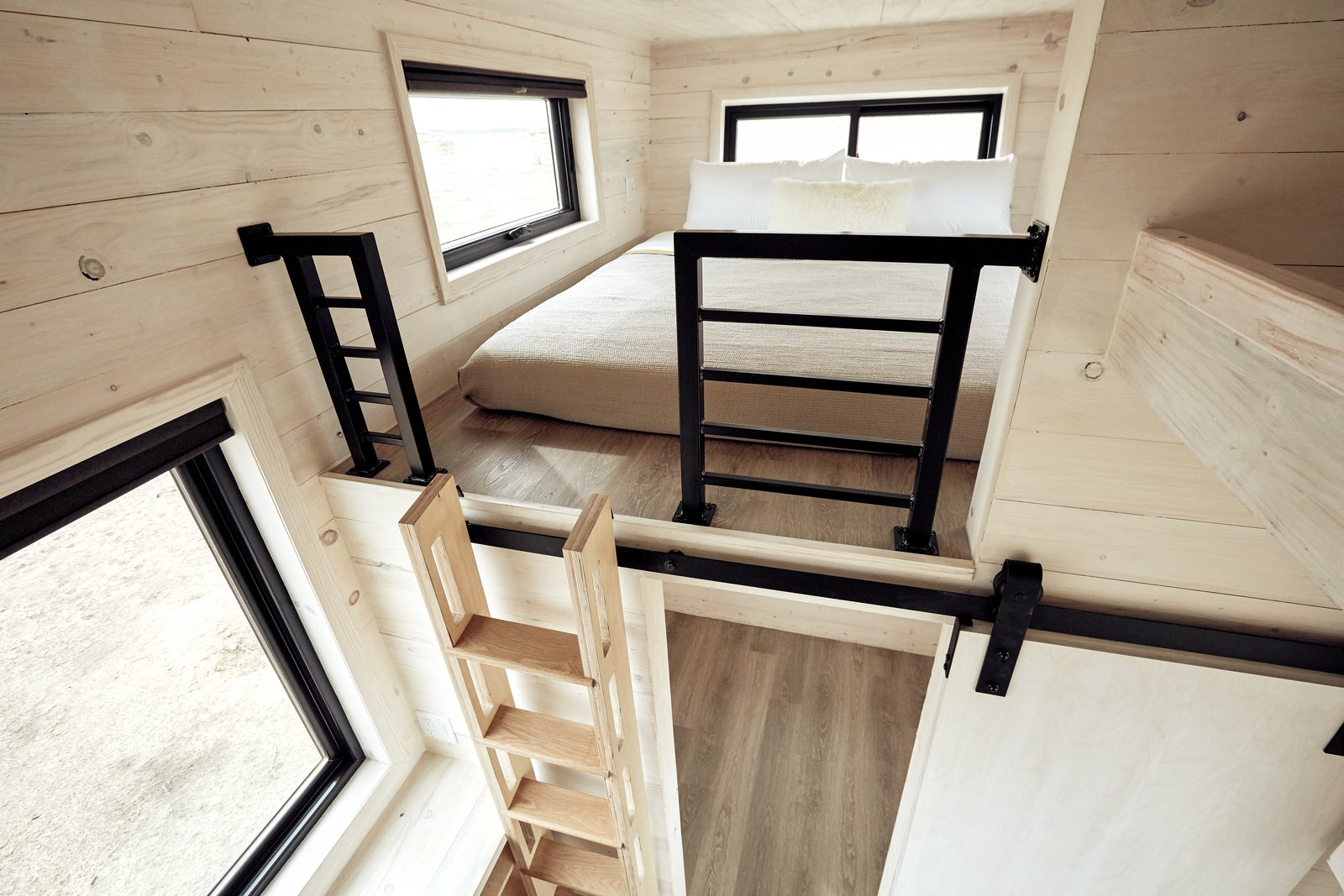 The loft ladder can be hung against the wall as shown or secured at an angle for ergonomic climbing. The master loft easily fits a king size bed. Ladder and built-ins designed by Land Ark, cut and assembled by Twig Custom Builders.  Land Ark RV - Drake by Brian Buzarde