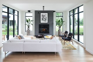The fireplace in Mississippi Modern by Charlie & Co. Design is offset by floor-to-ceiling windows—but not an ounce of coziness is lost.