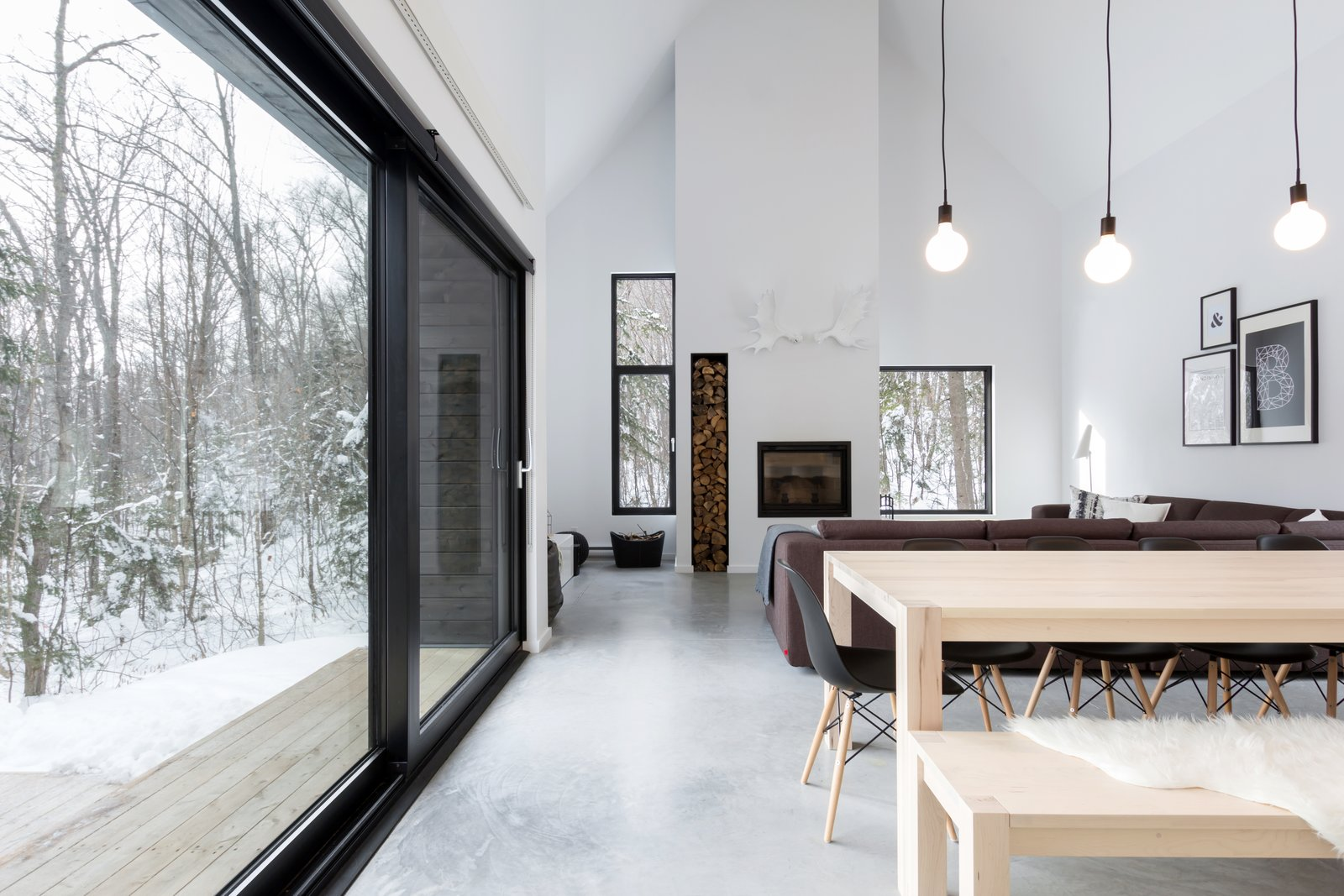 """Living Room, Concrete Floor, Pendant Lighting, and Wood Burning Fireplace Throughout the design, the site was quickly revealed as a powerful element of the project. By choosing carefully the location and size of each window, external views were highlighted, and the atmosphere created by natural light is pleasant throughout the whole day. As for the position of the large sliding door, it was """" pushed """" toward the main interior open space with the intention of subtly separating the internal functions while creating a outside protected space. All these intentions ultimately aim to capture the essence of this project: the surrounding nature and wildlife.  Photos from Reno ideas"""