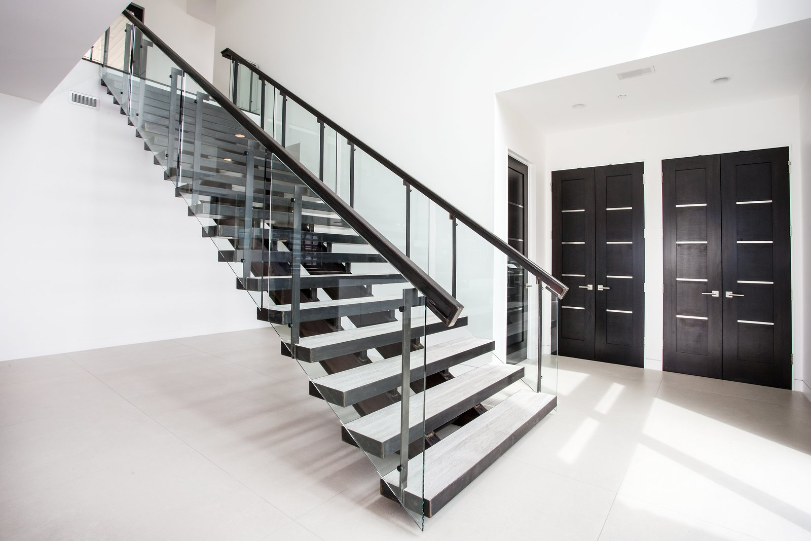 Staircase and Glass Railing Custom metal fabrication with glass railing on these stairs echo the clean, modern look that emanates throughout the home.   Purple Sage