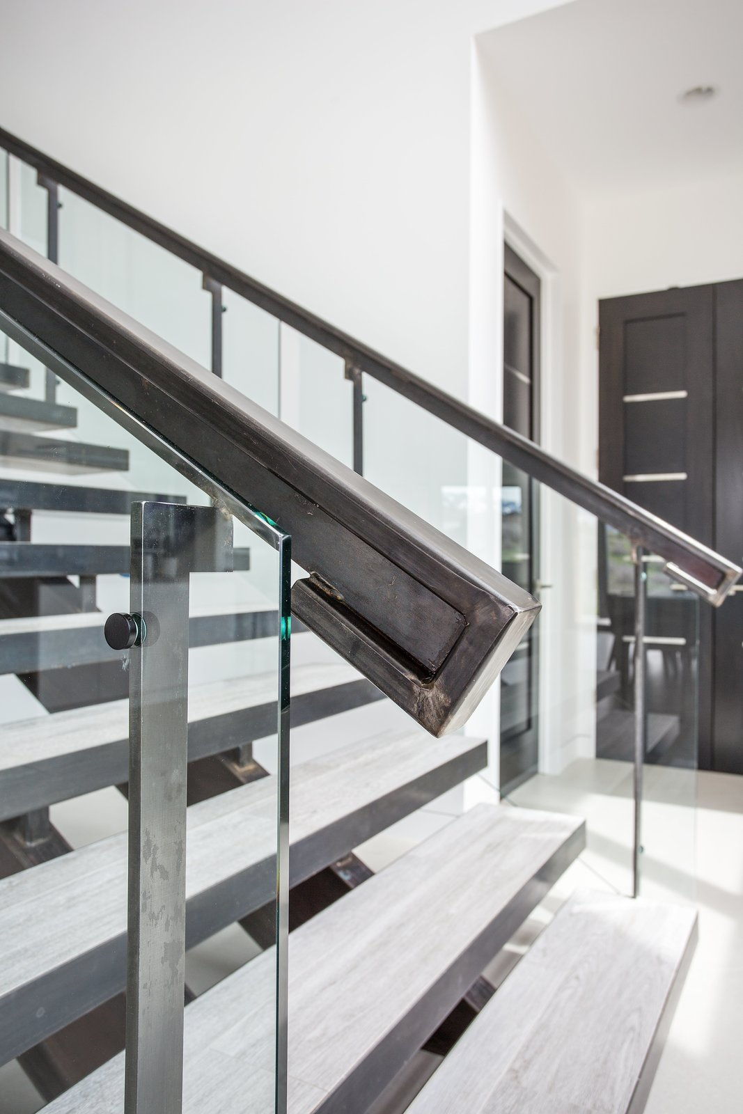 Staircase, Glass Railing, and Metal Railing Pairing glass and metal to create a showpiece staircase.  Purple Sage