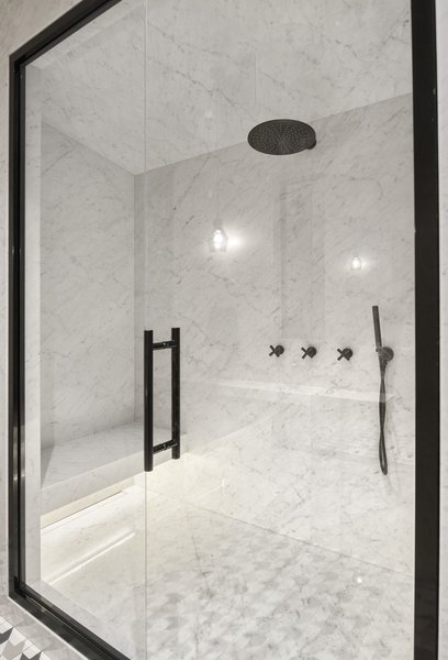 Minimalist black fixtures adorn the shower.